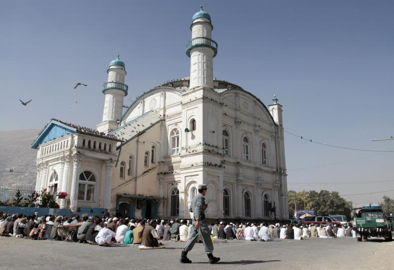 An Afghan policeman walks outsid Shah-e- Dushamshera's mosque where Afghans wait to offer the Eid al-Fitr's prayers that marks the end of holy fasting month of Ramadan in Kabul, Afghanistan, Sunday, Aug. 19, 2012. (AP Photo/Musadeq Sadeq)