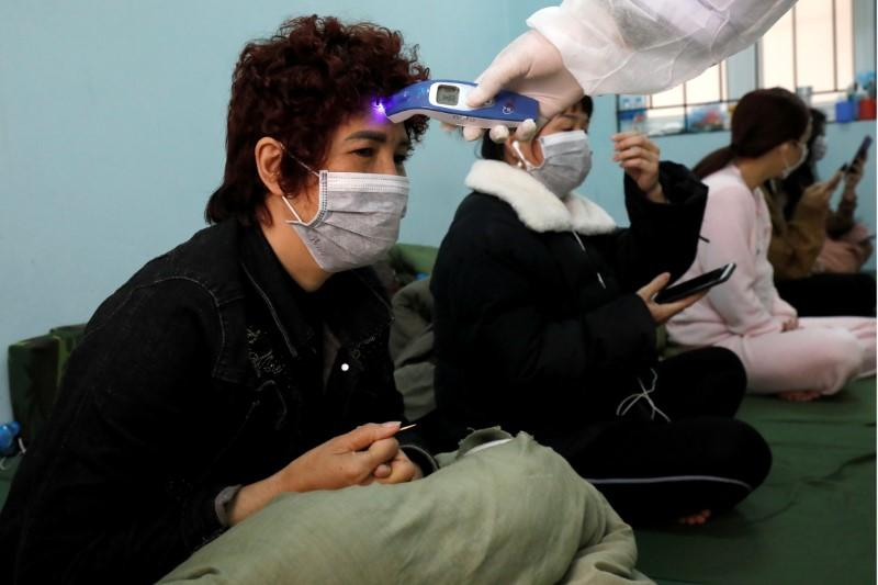 FILE PHOTO: Military doctors check people, who came back from China, as they stay quarantined at a military base in Lang Son province, Vietnam