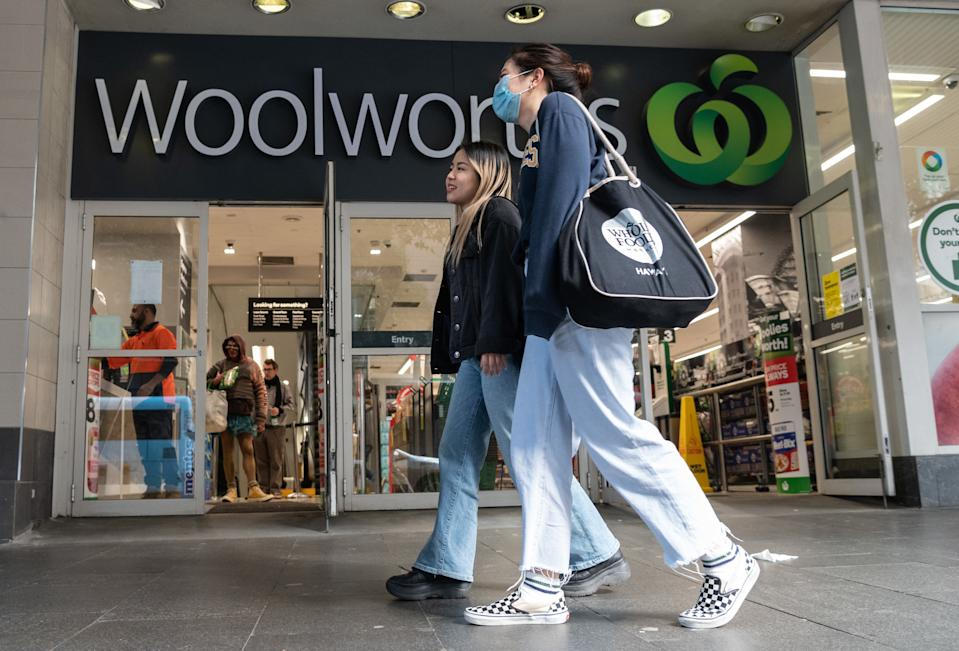 A person wearing a face mask in front of a Woolworths shop. Source: AAP
