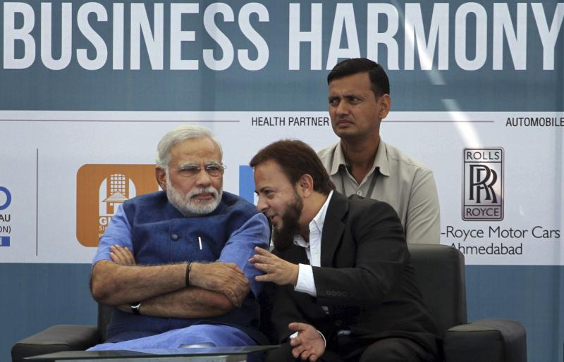 FILE- In this Feb. 7, 2014 file photo, Gujarat state Chief Minister Narendra Modi, left, listens to Zafar Sareshwala, a Muslim businessman who runs a BMW dealership in Ahmedabad, during an inaugural event of a three-day conclave on business harmony in Ahmadabad, India. Sareshwala said he was a staunch opponent of Modi after the 2002 riots but was eventually won over after meeting him and seeing the results of his infrastructure campaign. To some, the man in pole position to be India's next prime minister is a visionary reformer, while to others he's an autocrat in bed with big business cronies. Perhaps nowhere are opinions of Narendra Modi more polarized than in Gujarat, the western state he's led for more than decade and that is now touted as a model of prosperity for all of India to emulate. (AP Photo/Ajit Solanki, File)