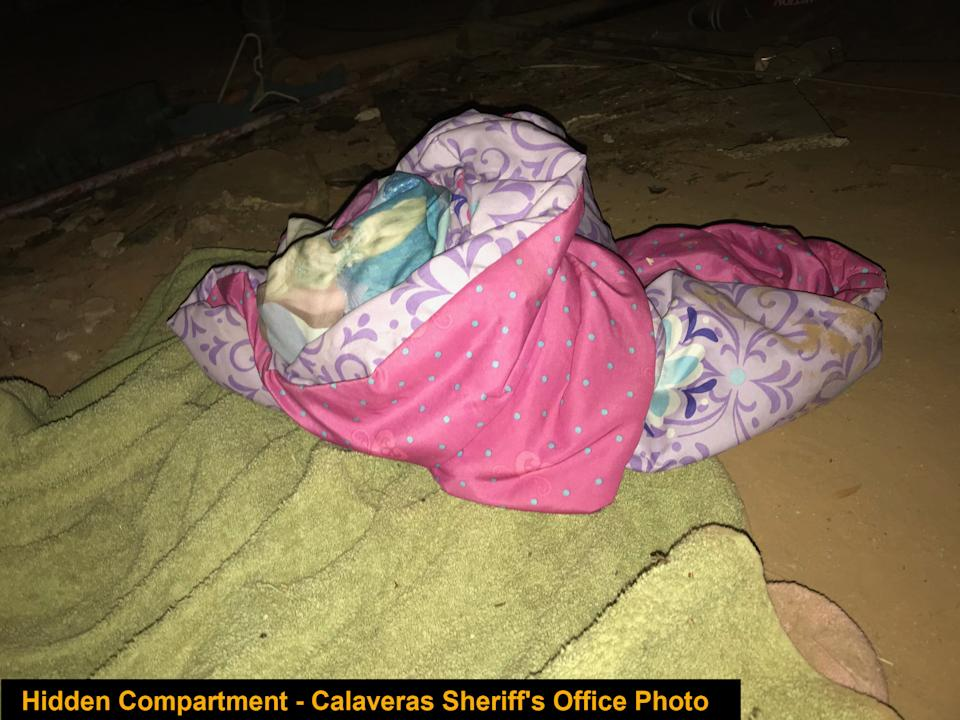 Pink bedding in the makeshift sleeping space on the dirt floor.