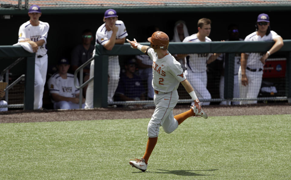 Kody Clemens flashes the Hook'em Horns at the Tennessee dugout as he rounds the base after hitting a home run in the third inning of an NCAA college super regional baseball game. (AP Photo/Eric Gay)