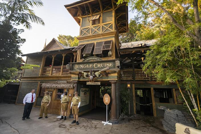 Three people in khaki shorts and shirts and a man in a dress shirt and tie outside a building with a Jungle Cruise sign on it