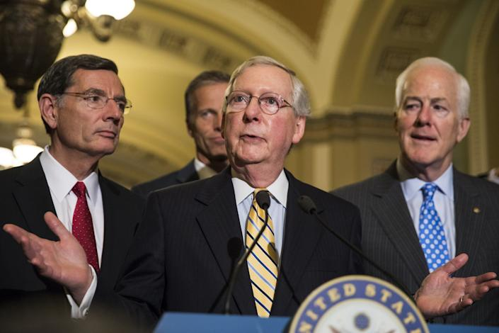 Senate Majority Leader Mitch McConnell, center, speaks alongside Sens. John Barrasso, left, John Cornyn, right, and John Thune, rear, after the Senate narrowly passed the motion to proceed for the replacement of the Affordable Care Act on July 25, 2017.