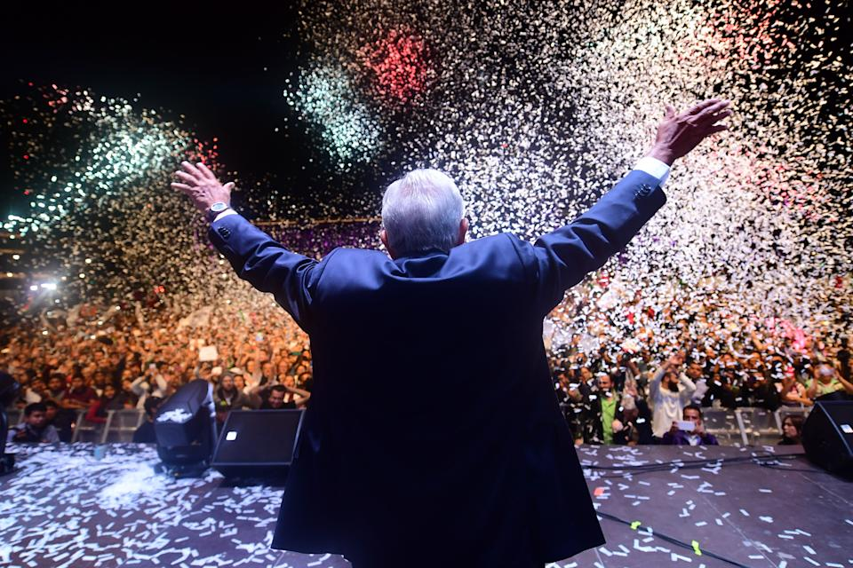 TOPSHOT - Newly elected Mexico's President Andres Manuel Lopez Obrador (C), running for 'Juntos haremos historia' party, cheers his supporters at the Zocalo Square after winning general elections, in Mexico City, on July 1, 2018. (Photo by PEDRO PARDO / AFP)        (Photo credit should read PEDRO PARDO/AFP/Getty Images)