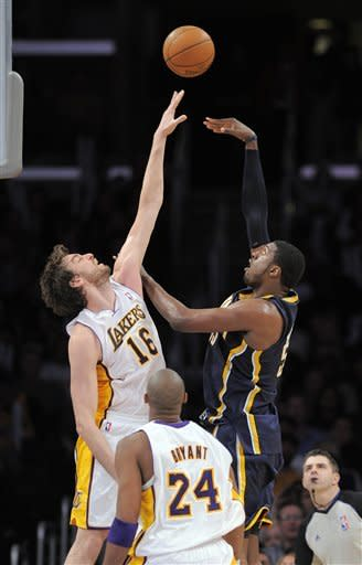 Indiana Pacers center Roy Hibbert, right, puts up a shot as Los Angeles Lakers forward Pau Gasol, left, of Spain defends and guard Kobe Bryant looks on during the second half of their NBA basketball game, Sunday, Jan. 22, 2012, in Los Angeles. The Pacers won 96-98. (AP Photo/Mark J. Terrill)