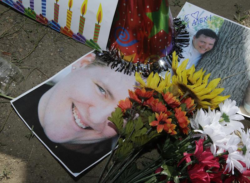 """Photographs of theater shooting victim Alex Sullivan are shown, Saturday, July 21, 2012, at a memorial near the movie theater in Aurora, Colo. Twelve people were killed and dozens were injured in the attack early Friday at the packed theater during a showing of the Batman movie, """"The Dark Knight Rises."""" Police have identified the suspected shooter as James Holmes, 24. (AP Photo/Ted S. Warren)"""