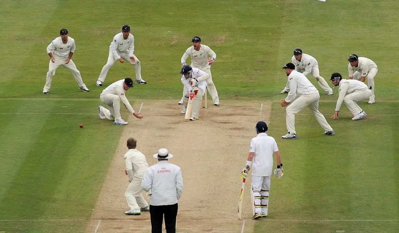 New Zealand players surround the bat as England's Steven Finn bats during the first test at Lord's Cricket Ground, London.
