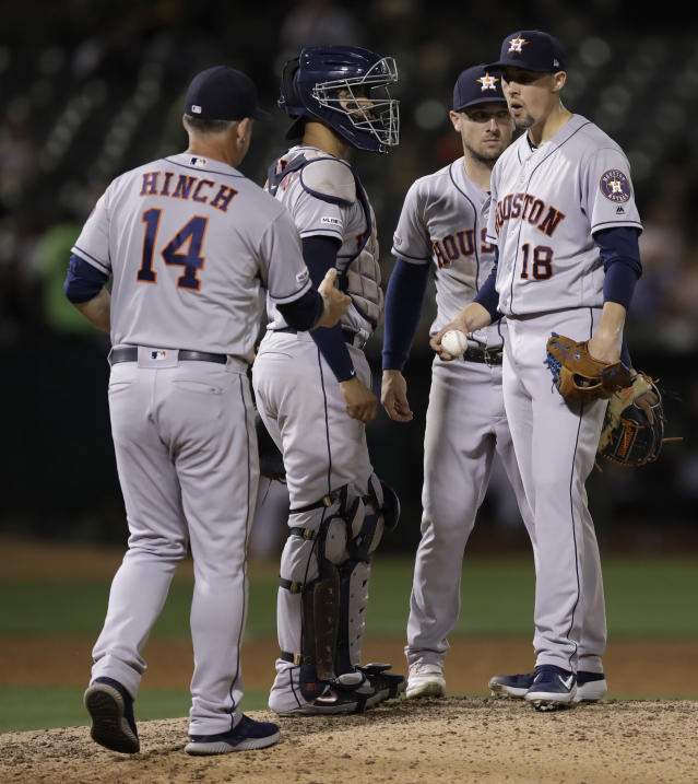 Houston Astros pitcher Aaron Sanchez (18) hands the ball to manager AJ Hinch (14) as he is removed during the sixth inning of the team's baseball game against the against the Oakland Athletics on Thursday, Aug. 15, 2019, in Oakland, Calif. (AP Photo/Ben Margot)