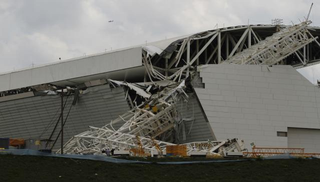 """Workers stand near a crane that collapsed on the site of the Arena Sao Paulo stadium, known as """"Itaquerao"""", which will host the opening soccer match of the 2014 World Cup, in Sao Paulo November 27, 2013. A crane collapsed on Wednesday at the construction site of a future World Cup soccer stadium in Sao Paulo, Brazil, killing at least three people and causing damage to the structure, local media said. REUTERS/Nacho Doce (BRAZIL - Tags: SPORT SOCCER DISASTER TPX IMAGES OF THE DAY WORLD CUP)"""