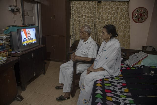 An elderly Indian couple watch Prime Minister Narendra Modi address the nation (Anupam Nath/AP)