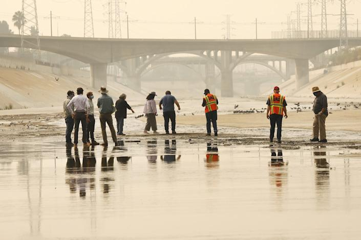 People stand in the shallow trickle of water in the concrete LA River channel