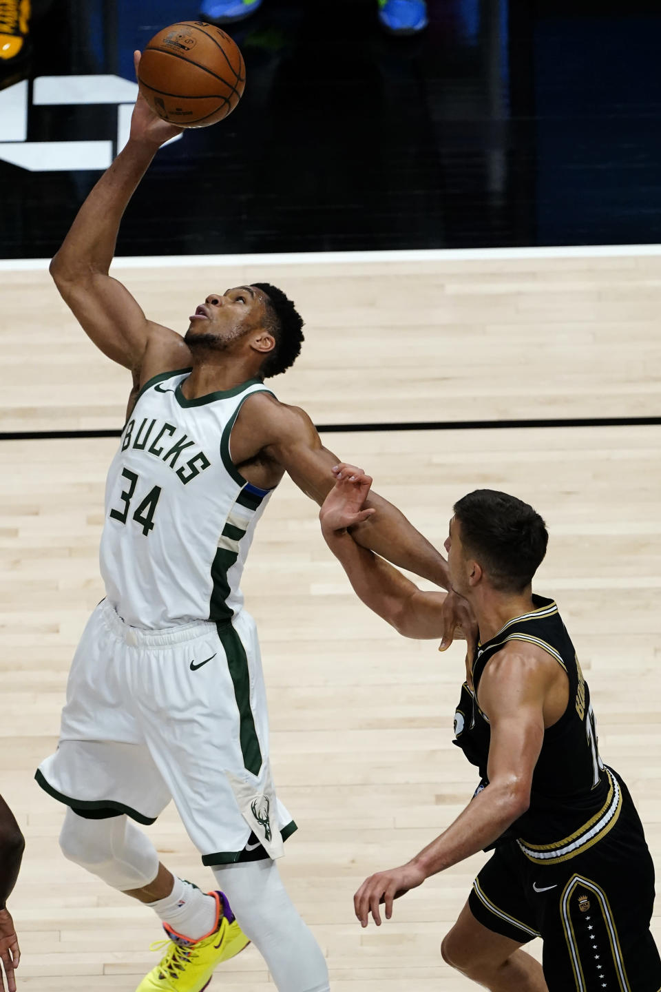 Milwaukee Bucks forward Giannis Antetokounmpo (34) reaches for the ball next to Atlanta Hawks guard Bogdan Bogdanovic (13) during the first half of an NBA basketball game Thursday, April 15, 2021, in Atlanta. (AP Photo/John Bazemore)
