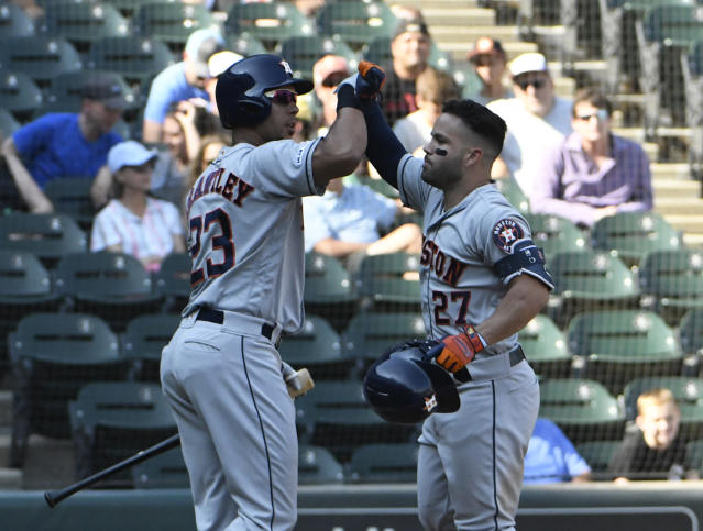 Houston Astros' Jose Altuve (27) is greeted by Michael Brantley (23) after hitting a home run against the Chicago White Sox during the third inning of game one of a baseball doubleheader, Tuesday, Aug. 13, 2019, in Chicago. (AP Photo/David Banks)