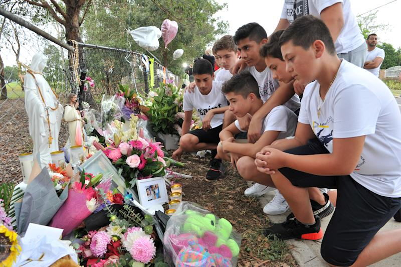 Schoolmates of one of the boys killed gather to pay their respects at a makeshift memorial at the site of an accident which killed four children in Oatlands.