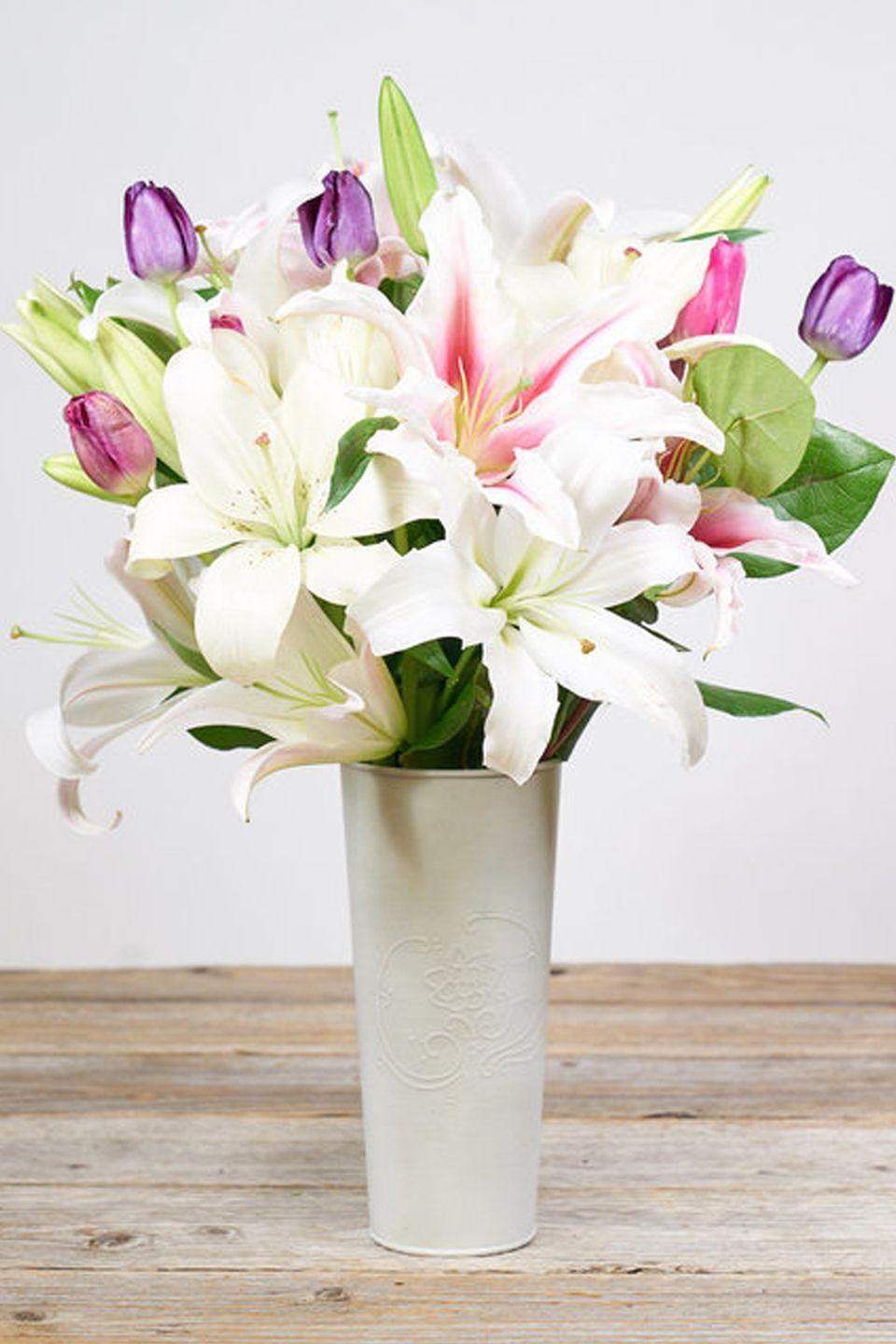 """<p>Easter lilies are some of the most common flowers used to celebrate this holiday and this arrangement pairs them with pink and purple tulips to keep them from feeling boring.<strong><em><br></em></strong></p><p><strong><em>West Elm Baro Vase, $35</em></strong> <a class=""""link rapid-noclick-resp"""" href=""""https://go.redirectingat.com?id=74968X1596630&url=https%3A%2F%2Fwww.westelm.com%2Fproducts%2Fbarro-vases-d7627%2F%3Fpkey%3Dcvase&sref=https%3A%2F%2Fwww.housebeautiful.com%2Fentertaining%2Fflower-arrangements%2Fg19409803%2Feaster-flower-arrangements%2F"""" rel=""""nofollow noopener"""" target=""""_blank"""" data-ylk=""""slk:BUY NOW"""">BUY NOW</a></p>"""