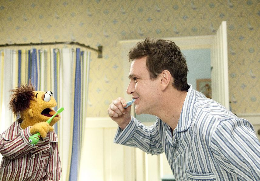 """In this film publicity image released by Disney, muppet character Walter, left, and Jason Segel are shown with the muppet characters in a scene from """"The Muppets."""" (AP Photo/Disney Enterprises, Patrick Wymore)"""