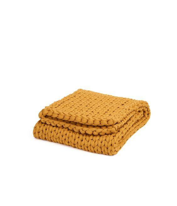 """A <a href=""""https://www.architecturaldigest.com/story/best-weighted-blankets?mbid=synd_yahoo_rss"""" rel=""""nofollow noopener"""" target=""""_blank"""" data-ylk=""""slk:weighted blanket"""" class=""""link rapid-noclick-resp"""">weighted blanket</a> might relieve some of the post-move stress, plus it looks totally chic draped over the foot of a bed. The Bearaby Cotton Napper is one of our favorite weighted blankets, and you can get it in navy, white, green, pumpkin, gray, blush, burgundy, or yellow (pictured). $249, Bearaby. <a href=""""https://bearaby.com/products/the-napper?variant=32164549394521"""" rel=""""nofollow noopener"""" target=""""_blank"""" data-ylk=""""slk:Get it now!"""" class=""""link rapid-noclick-resp"""">Get it now!</a>"""