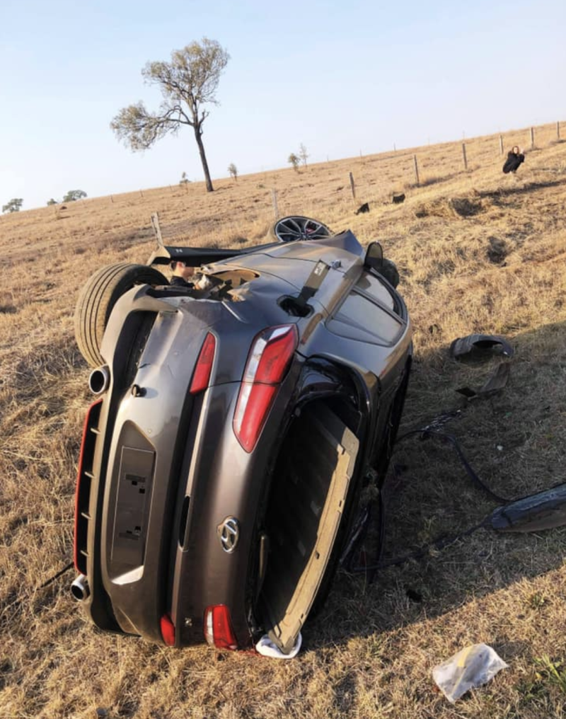 The Hyundai on its side on the roadside.