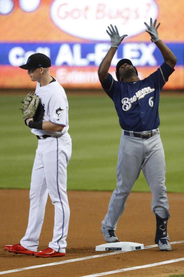 Milwaukee Brewers' Lorenzo Cain (6) celebrates a base hit next to Miami Marlins right fielder Garrett Cooper during the first inning of a baseball game, Thursday, Sept. 12, 2019, in Miami. (AP Photo/Wilfredo Lee)