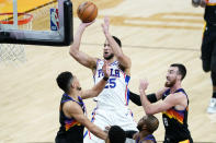 Philadelphia 76ers guard Ben Simmons (25) shoots over Phoenix Suns guard Devin Booker, left, during the first half of an NBA basketball game, Saturday, Feb. 13, 2021, in Phoenix.(AP Photo/Matt York)