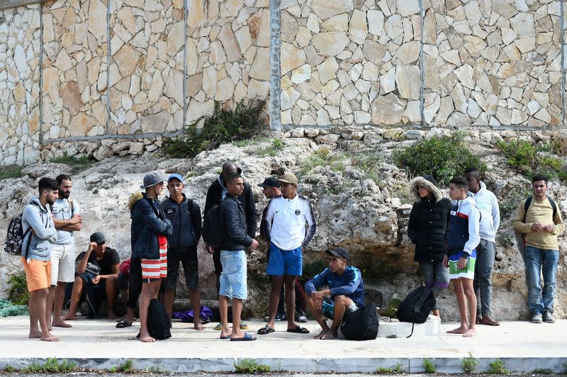 FILE PHOTO: Migrants are seen after disembarking from a wooden boat on the island of Lampedusa