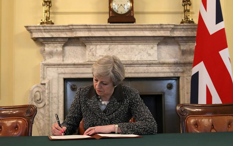 Theresa May signs the official letter to Donald Tusk, European Council President, invoking Article 50 - Credit: Christopher Furlong/Getty Images/WPA Pool