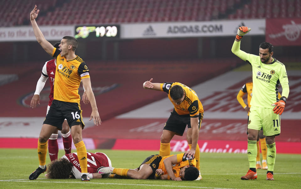 Players gesture to medical staff after a head clash between Arsenal's David Luiz, bottom left, and Wolverhampton Wanderers' Raul Jimenez during the English Premier League soccer match between Arsenal and Wolverhampton Wanderers at Emirates Stadium, London, Sunday, Nov. 29, 2020. (John Walton/Pool via AP)