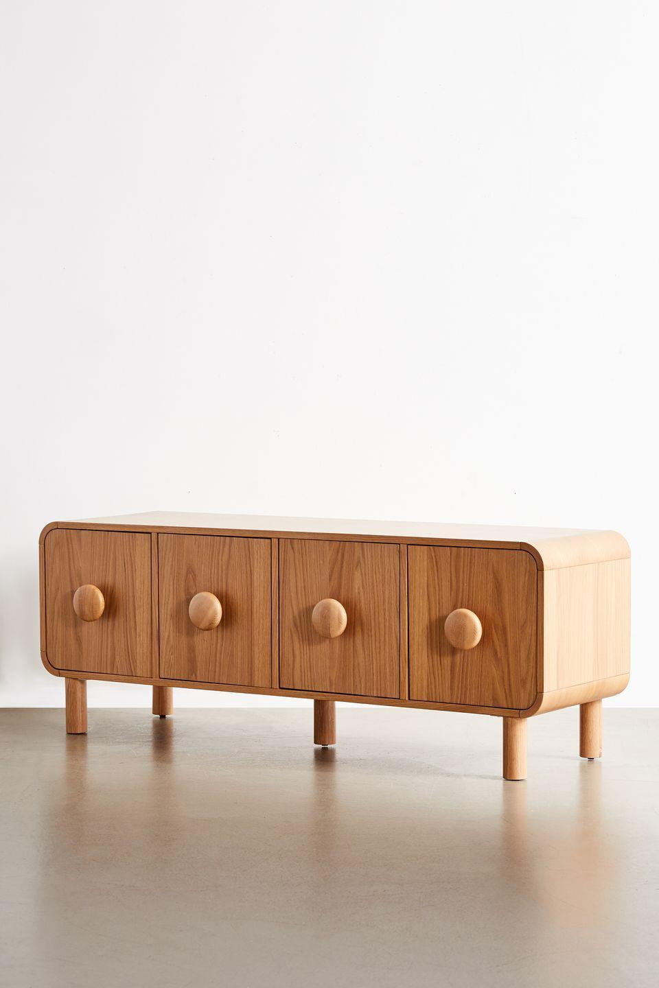 """<p>Oversized round handles and chunky legs give this mid-century-inspired oak veneer media cabinet an up-to-date look and feel. Inside, shelves provide space to house those unsightly black boxes, wires and hubs. £449, <a href=""""https://www.urbanoutfitters.com/en-gb/?ref=logo"""" rel=""""nofollow noopener"""" target=""""_blank"""" data-ylk=""""slk:urbanoutfitters.com"""" class=""""link rapid-noclick-resp"""">urbanoutfitters.com</a></p>"""
