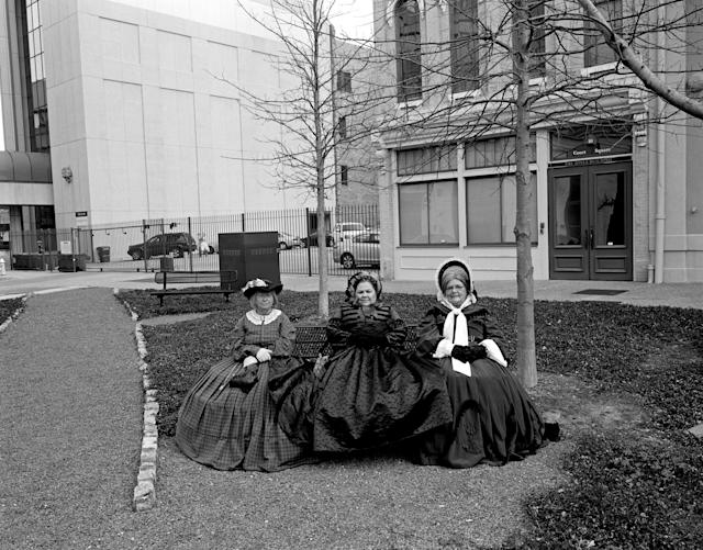 "<p>""American Memory"": Montgomery, Ala., 2011. To celebrate the 150th anniversary of the inauguration of President Jefferson Davis, Civil War reenactors hold a rally in downtown Montgomery, the first capitol of the Confederacy. Perhaps by coincidence, these women, waiting for the rally to begin, are sitting on a park bench where Rosa Parks boarded the city bus she was arrested on in 1955, which helped launch the civil rights movement. (© Andrew Lichtenstein from ""War Is Only Half the Story,"" the Aftermath Project & Dewi Lewis Publishing) </p>"