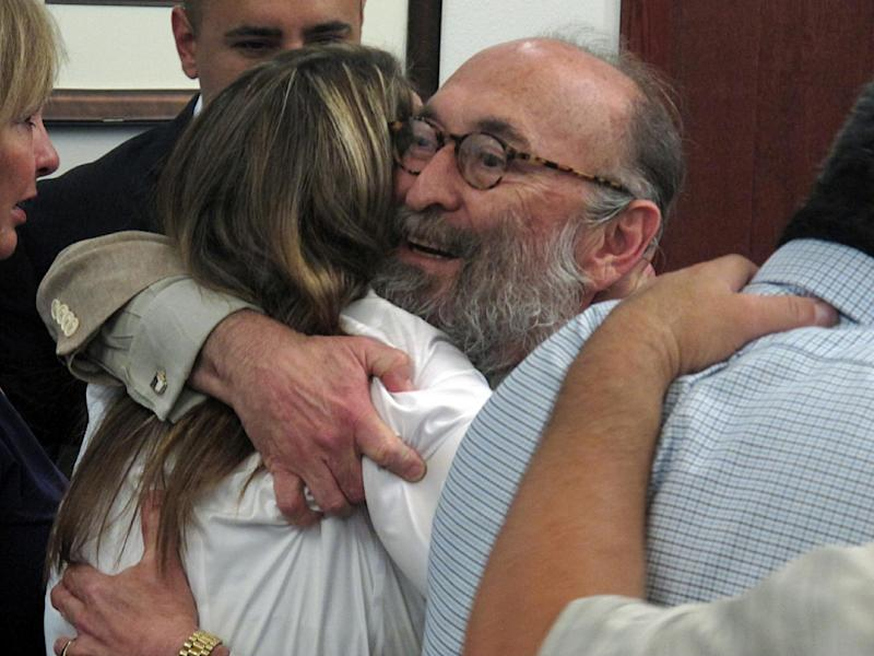 In this July 16, 2013 photo, Heather Chavez, current wife of former Albuquerque police officer Levi Chavez, is shown hugging defense attorney David Serna in Sandoval District Court in Bernalillo, N.M., after a jury acquitted Levi Chavez of murdering his then-wife, 26-year-old Tera Chavez, in 2007 and making it look like a suicide. The jury's decision Tuesday came after more than 10 hours of deliberations and a month long trial detailing Chavez's many affairs, charges of a botched investigation and allegations of a police cover-up. (AP Photo/Russell Contreras)