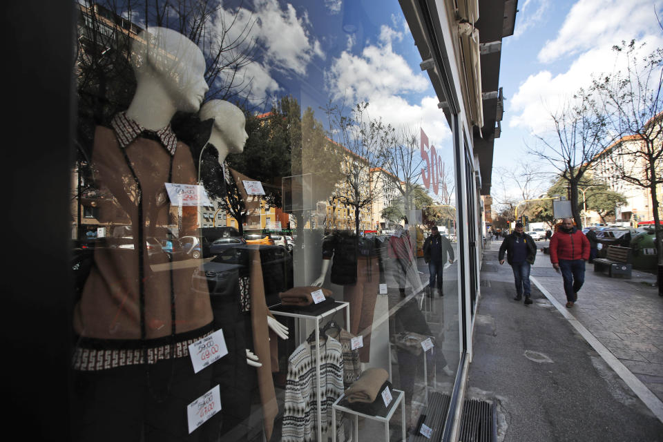 People are reflected on the window of a closed shop in a main shopping street in downtown Rome, Monday, March 15, 2021. Half of Italy's regions have gone into the strictest form of lockdown in a bid to curb the latest spike in coronavirus infections that have brought COVID-19 hospital admissions beyond manageable thresholds.(AP Photo/Alessandra Tarantino)