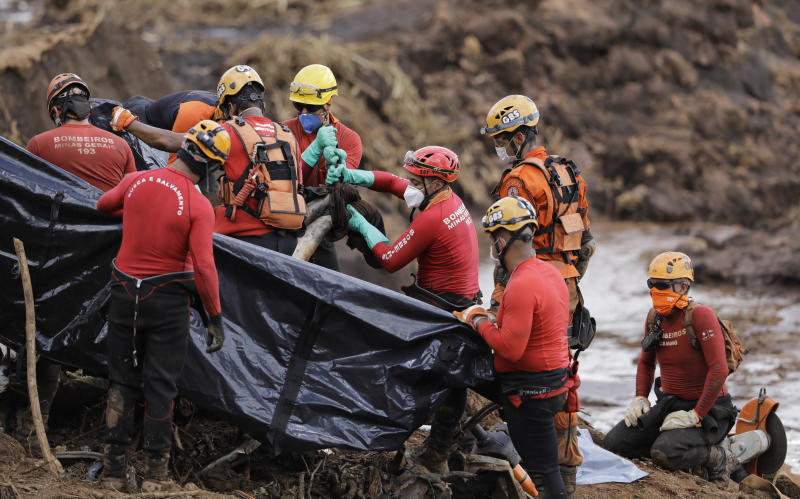 Firefighters pull a body from the mud days after a dam collapse in Brumadinho, Brazil, Monday, Jan. 28, 2019. Firefighters on Monday carefully moved over treacherous mud, sometimes walking, sometimes crawling, in search of survivors or bodies four days after a dam collapse that buried mine buildings and surrounding neighborhoods with iron ore waste. (AP Photo/Leo Correa)