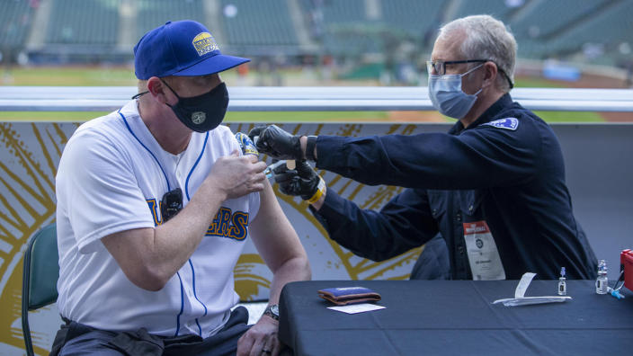 Seattle Fire Department EMT Bill Allemann gives Chris Hoffman, of Kent, Washington a Johnson & Johnson Covid-19 vaccine during batting practice before a game between the Seattle Mariners and Baltimore Orioles at T-Mobile Park. (Joe Nicholson-USA TODAY Sports via Reuters)