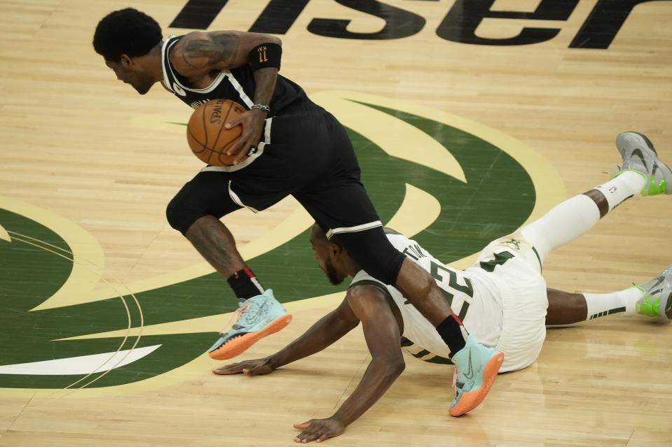 Brooklyn Nets' Kyrie Irving steals the ball from Milwaukee Bucks' Khris Middleton during the first half of Game 4 of the NBA Eastern Conference basketball semifinals game Sunday, June 13, 2021, in Milwaukee. (AP Photo/Morry Gash)