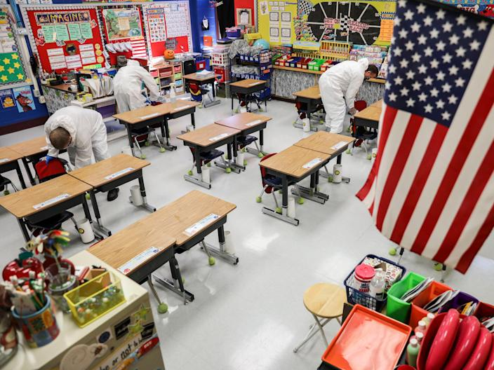A crew of custodial staff clean a classroom at Richard A Simpson Elementary School in Arnold, Missouri, on Thursday 5 November 2020 ((Associated Press))