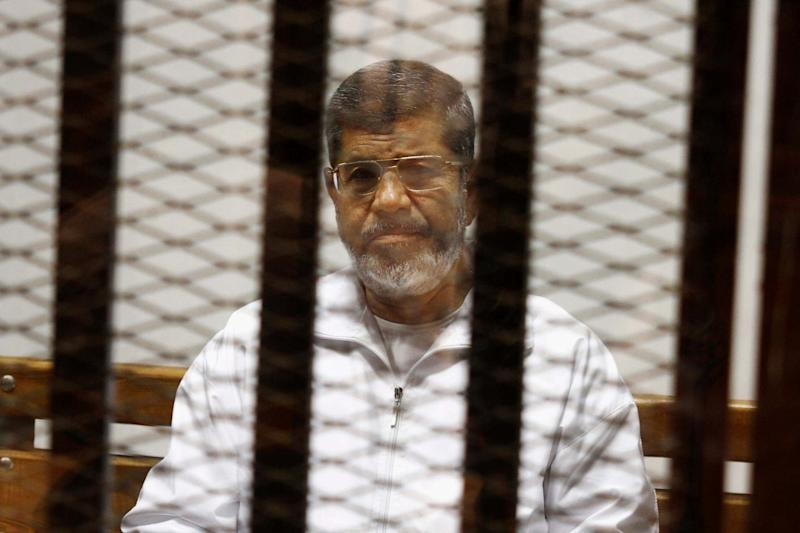 Mr Morsi pictured in 2014 in a defendant cage in the Police Academy courthouse in Cairo (AP)