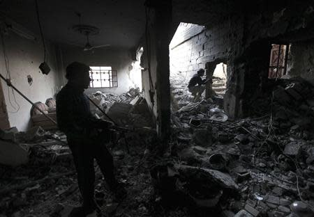 Free Syrian Army fighters take up position inside a damaged house filled with debris in Deir al-Zor, eastern Syria November 14, 2013. REUTERS/Khalil Ashawi