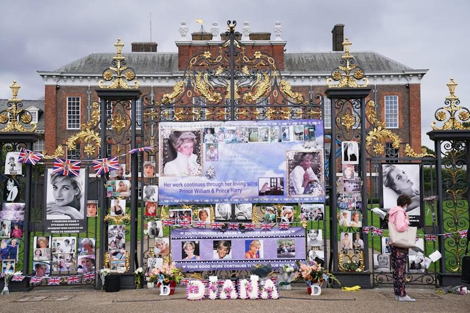 People look at tributes left at the gates of Kensington Palace in London on the 24th anniversary of the death of Diana, Princess of Wales. Picture date: Tuesday August 31, 2021. (PA Wire)