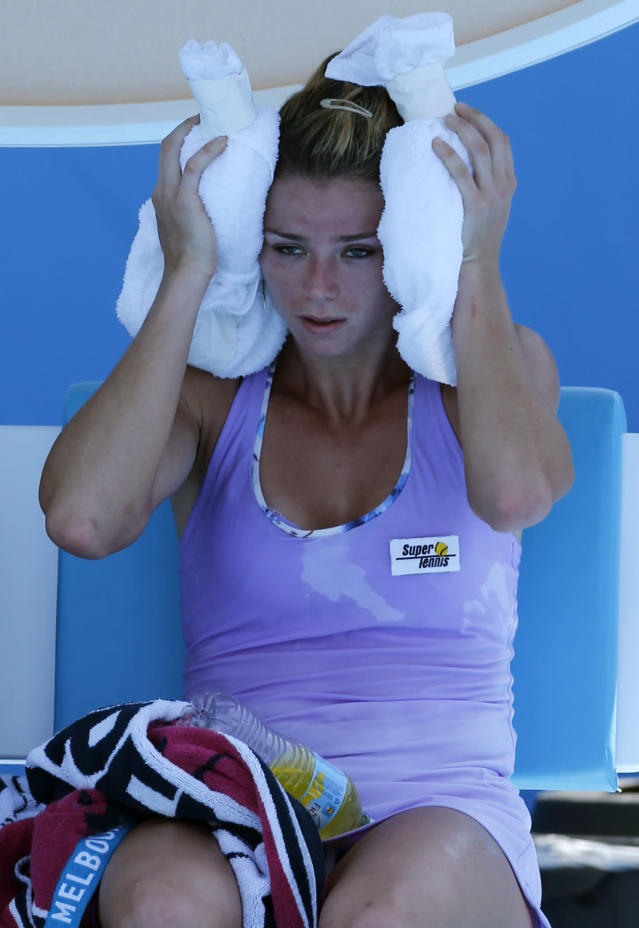 Camila Giorgi of Italy cools off with ice pack during a break as she plays Storm Sanders of Australiia during their first round match at the Australian Open tennis championship in Melbourne, Australia, Tuesday, Jan. 14, 2014. (AP Photo/Shuji Kajiyama)