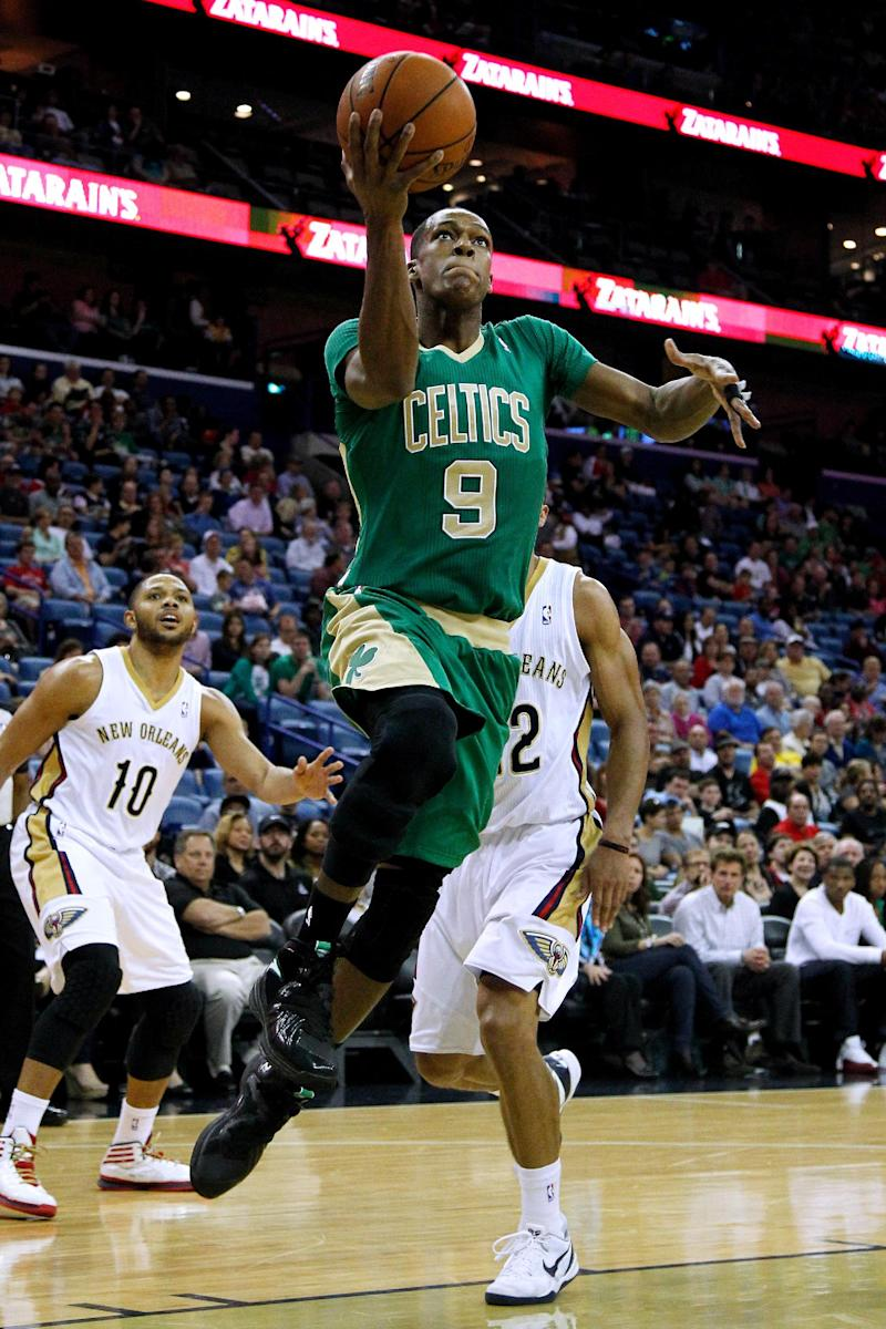 Boston Celtics guard Rajon Rondo (9) drives to the basket against New Orleans Pelicans guard Eric Gordon (10) and New Orleans Pelicans guard Brian Roberts, right, during the first half of an NBA basketball game in New Orleans, Sunday, March 16, 2014. (AP Photo/Jonathan Bachman)