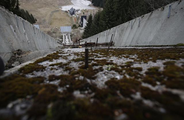 In this picture taken Friday, Feb. 21, 2014, the abandoned ski jumping facility is seen covered in moss at Mt. Igman near Bosnian capital of Sarajevo. Wartime destruction and negligence have turned most of Sarajevo's 1984 Winter Olympic venues into painful reminders of the city's golden times. The world came together in the former Yugoslavia in 1984 after the West had boycotted the 1980 Olympics in Moscow and Russia boycotted the 1984 Summer Games in Los Angeles. Just eight years later, the bobsleigh and luge track on Mount Trbevic was turned into an artillery position from which Bosnian Serbs pounded the city for almost four years. Today, the abandoned concrete construction looks like a skeleton littered with graffiti. (AP Photo/Amel Emric)