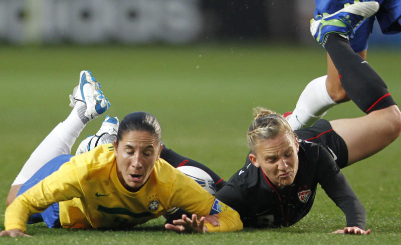 Daiane Menezes, left, of Brazil and Amy Rodriguez of the United States fall on the ground while battling for the ball during their Kirin Challenge Cup women's friendly soccer match in Chiba, eastt of Tokyo, Tuesday, April 3, 2012. (AP Photo/Koji Sasahara)