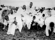 MAHATMA GANDHI (LEFT, BARE-CHESTED) AND HIS FOLLOWERS BREAKING THE SALT LAWS AT DANDI, INDIA. 1930. (Photo by PA Images via Getty Images)