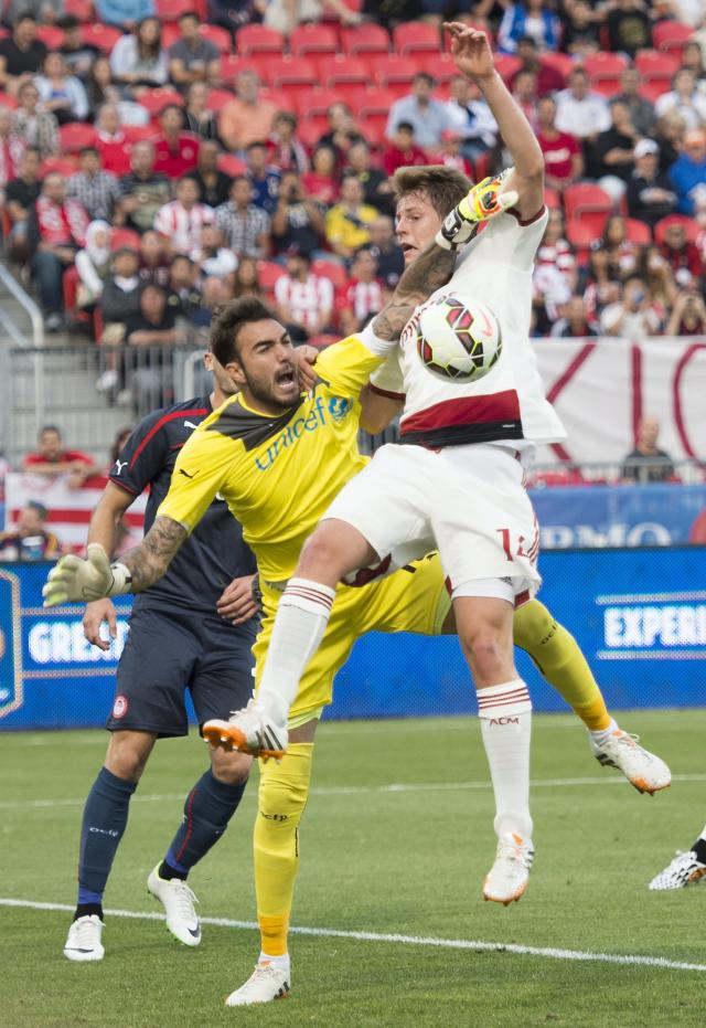 Olympiacos keeper Roberto Jimenez Gago, left, battles to make a save against AC Milan's Michelangelo Albertazzi during the first half of an International Champions Cup soccer match at BMO Field in Toronto on Thursday, July 24, 2014. (AP Photo/The Canadian Press, Darren Calabrese)