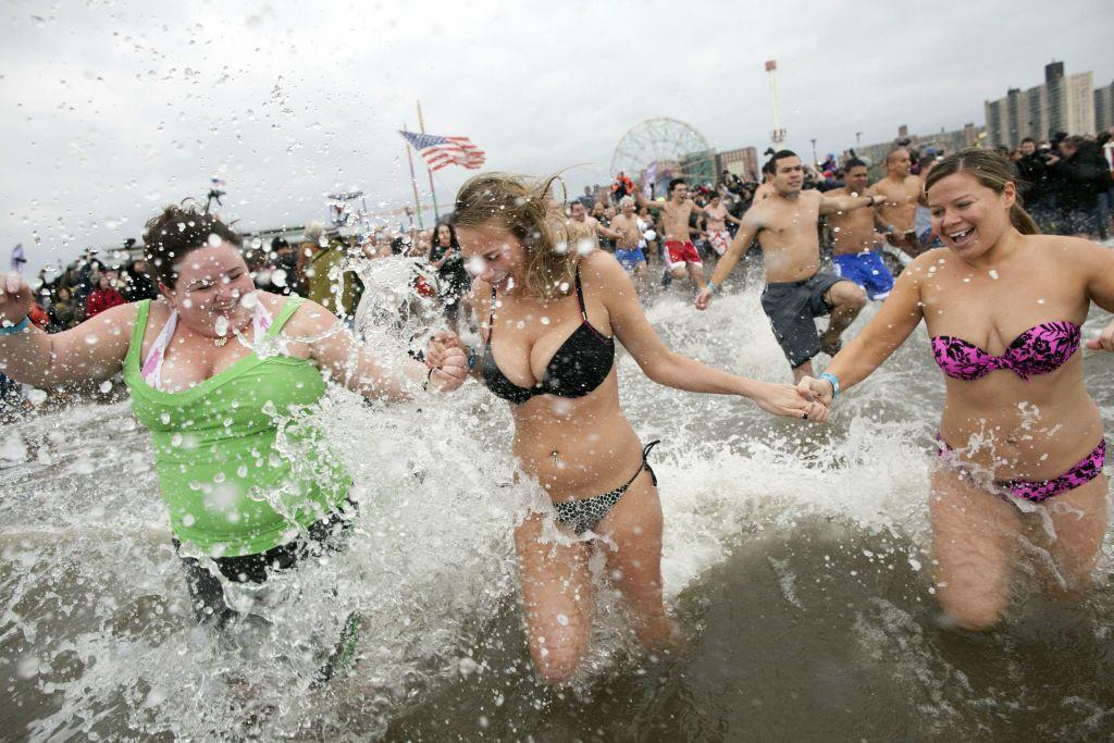 People enter the water while taking part in the Coney Island Polar Bear Club's annual New Year's Day Polar Bear Swim in New York's Coney Island January 1, 2013. The Coney Island Polar Bear Club is the oldest winter bathing organization in the U.S. and every New Years Day holds the winter plunge which attracts thousands of participants.