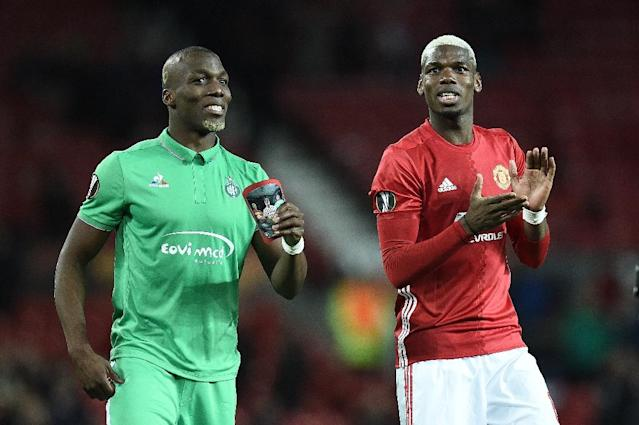 Saint-Etienne's defender Florentin Pogba (L) and his bother Manchester United's midfielder Paul Pogba applaud fans following the UEFA Europa League Round of 32 first-leg football match between Manchester United and Saint-Etienne on February 16, 2017 (AFP Photo/Oli SCARFF )