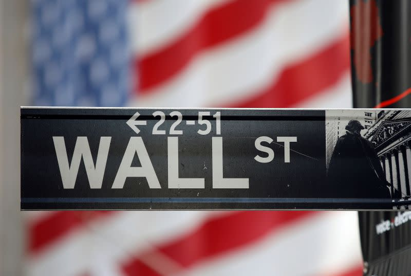 FILE PHOTO: FILE PHOTO: A sign for Wall Street is seen with a giant American flag in the background across from the New York Stock Exchange