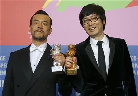 """Diao Yinan (R) director of """"Bai Ri Yan Huo"""" (Black Coal, Thin Ice) poses with his Golden Bear for Best Film next to actor Liao Fan (L) who poses with his Silver Bear for Best Actor during a news conference after the awards ceremony of the 64th Berlinale International Film Festival in Berlin February 15, 2014. REUTERS/Thomas Peter"""