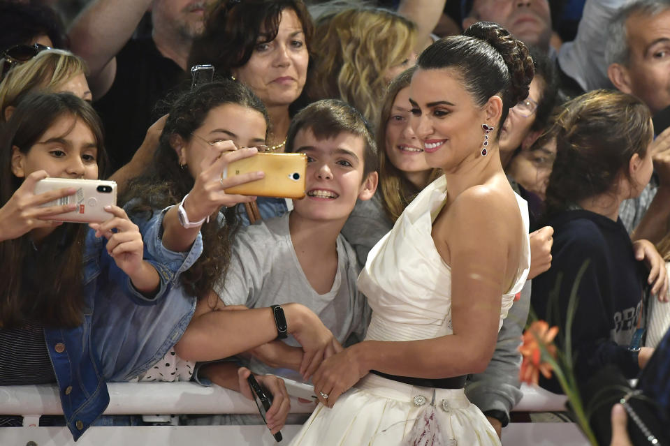 Actress Penelope Cruz poses for photographs with fans upon arrival for the premiere of the film 'Wasp Network' at the 67th San Sebastian Film Festival, in San Sebastian, northern Spain Friday, Sept. 27, 2019. (AP Photo/Alvaro Barrientos)